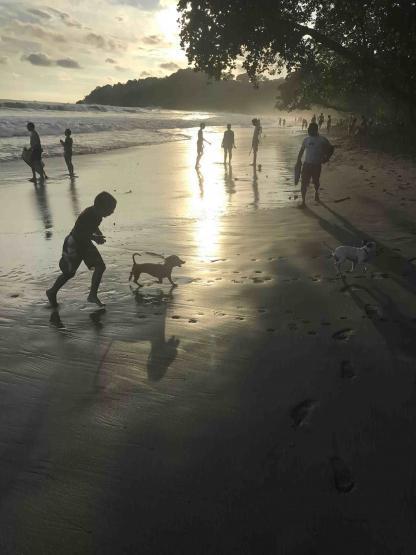 Enfant qui joue avec un chien à la plage de Manuel Antonio durant le couché du soleil au Costa Rica